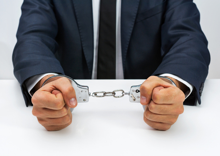 handcuffed: White young businessman handcuffed. Stock Photo