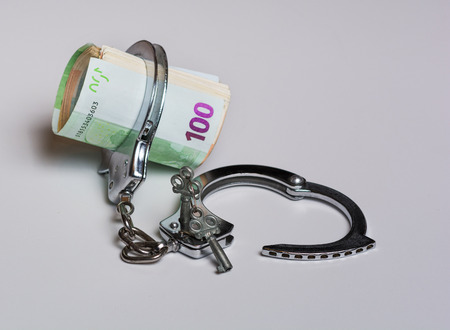 Money and handcuffs. Concept for corruption, fraud, money laundry