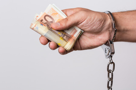 Male hand with handcuffs holding a lot of money