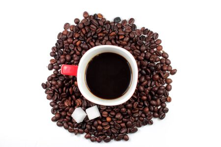 Red mug of coffee with roasted coffee beans and sugar lumps photo