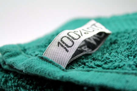 100% cotton label on green towel Stock Photo - 15024521