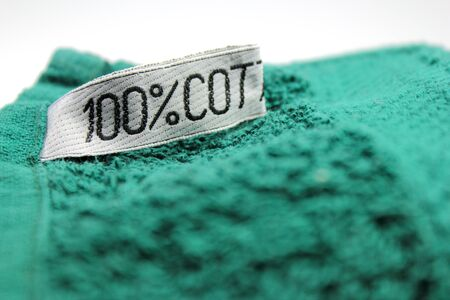100% cotton label on green towel Stock Photo