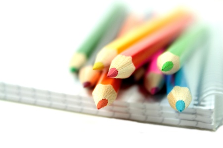 Colorful pencils with notebook on white background photo