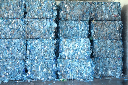 Bales of blue plastic bottles stacked at an undisclosed recycling facility  The plastic is gathered by color and type to be recycled