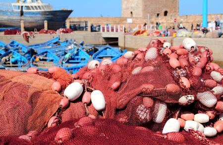 Morocco Essaouira  - fishing port with nets and buoys in the foreground and fleet of blue boats photo