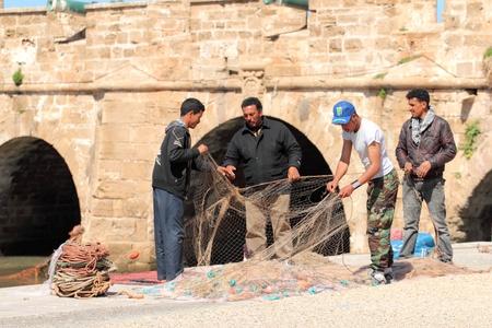 Fishermans repair fishing nets, Essaouira, Marocco