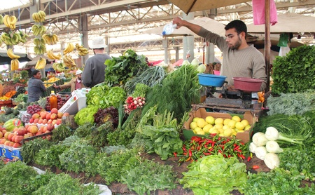 Seller man watering vegetables and fruits at market in Agadir, Morocco