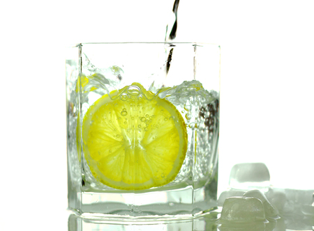 Pouring water on a glass with lemon photo