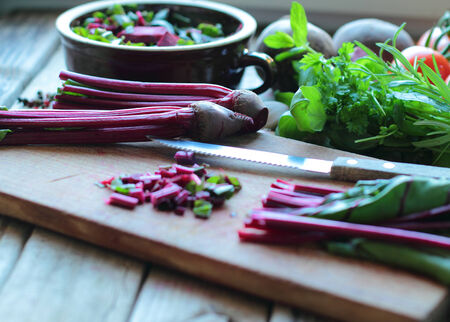 Cutting red beetroots with fresh herbs on the kitchen board Stock Photo