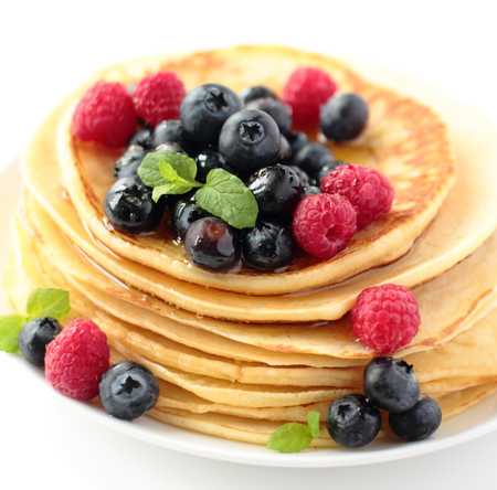 Stack of pancakes with fresh blueberry raspberry and honey