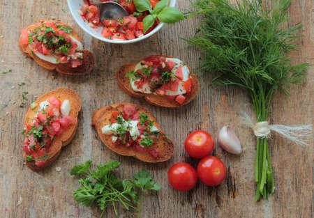 Bruschettas with fresh tomato, garlic, mozzarella and herbs Stock Photo