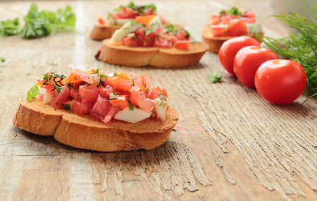 Fresh bruschetta with tomato, mozzarella, garlic and basil on wooden board