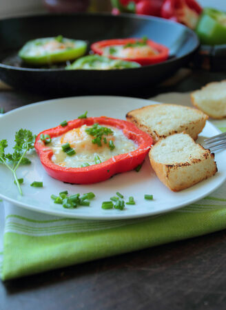 Fried eggs in peppers with white bread and fresh chive Stock Photo
