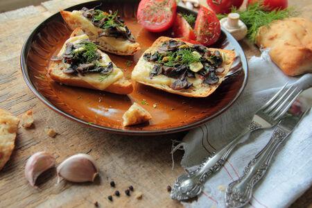 Plate with fresh bruschetta with mushrooms, cheese and garlic photo