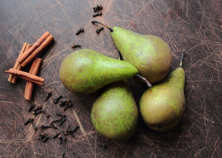Green pears on kitchen table with aromatic spices cinnamon and clove Stock Photo