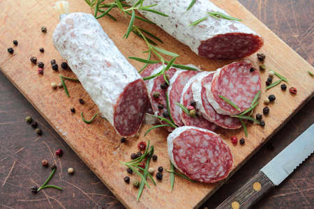 Salami on a cutting board with herbs