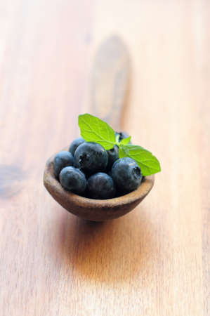 Blueberries with green leaf of mint on a wooden spoon Stock Photo