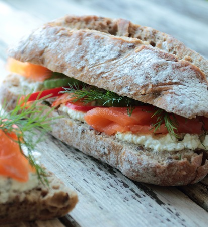 Sandwich with salmon, white cream cheese and vegetables for breakfast photo
