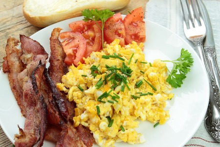 Tasty scrambled eggs with bacon and tomatoes