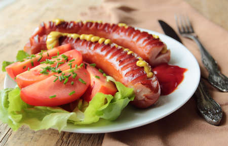 Plate with grilled sausages with fresh tomatoes Stock Photo