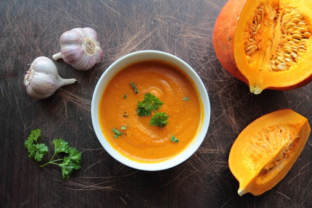 croutons: Pumpkin soup in a bowl with fresh pumpkins, garlic and parsley herbs