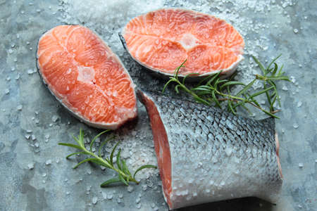 Fresh salmon filets with spices on old metal board photo