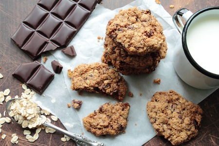 Oat cookies with chocolate and mug of milk