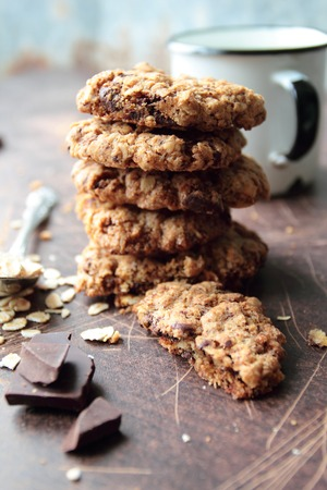 Stack of oat cookies with chocolate and mug of milk