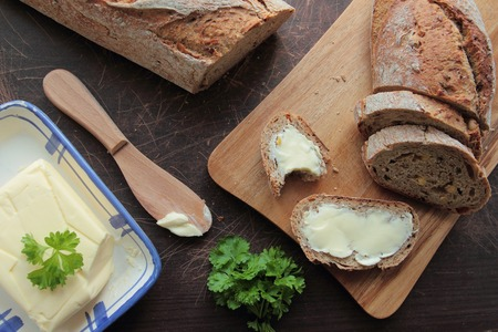 Bread on cutting board and slices of bread with butter Standard-Bild