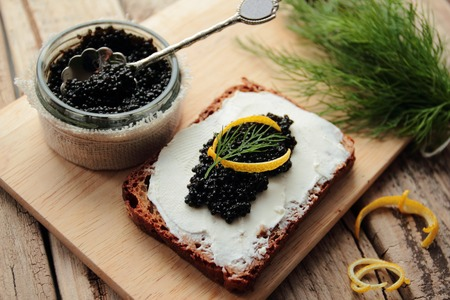 Black caviar on bread for appetizer. Caviar in small round jar