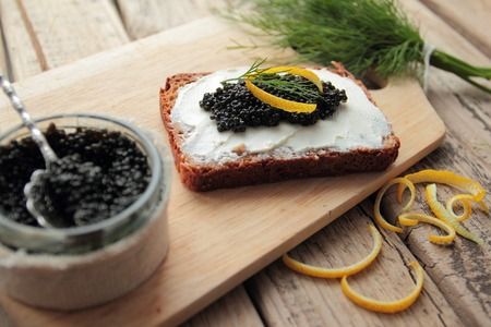 Black caviar and cream cheese on cutting bread Stock Photo