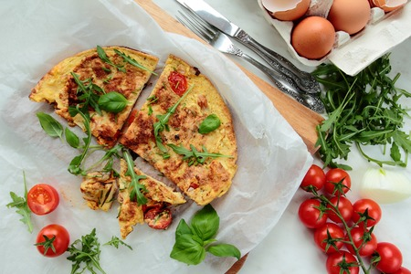 smithereens: Omelet with fresh rucola salad and tomatoes Stock Photo