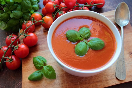 hot soup: Bowl with tasty tomato soup on wooden board