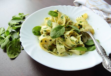 Pasta pappardelle with spinach leafs on white plate Stock Photo