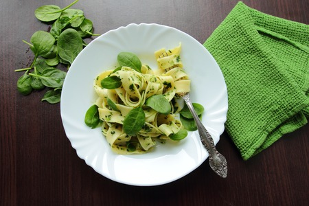 pasta sauce: White plate with tagliatelle pasta with fresh spinach