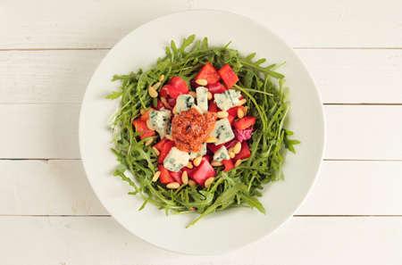 rukola: White plate with rucola salad, paprika, mildew cheese and tomato pesto