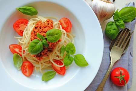 Spaghetti pasta with meat with bolognese sauce with fresh basil leafs