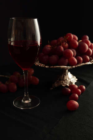 silver tray: Glass with red wine and grapes on a silver tray Stock Photo
