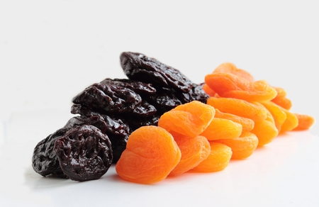 Dried apricots and plums isolated on white background Standard-Bild