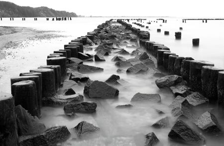 and the stakes: Old wooden stakes barrier with stones, Baltic Sea coast, Gdynia Babie Doly, Poland Stock Photo