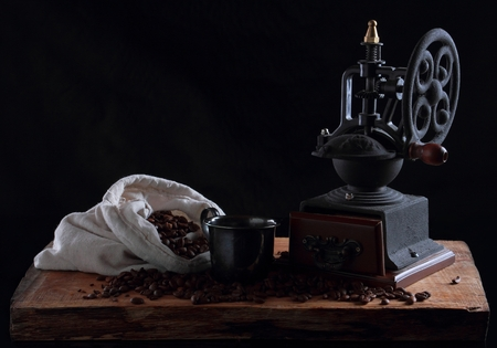 Vintage coffee grinder on a wooden desk. Black background Stock Photo