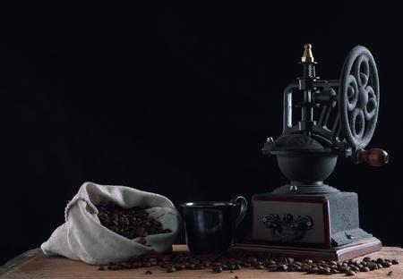 Old coffee bean grinder on the black background, studio shot