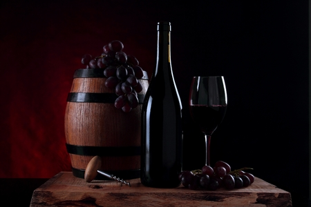 Bottle of red wine, grapes and wooden barrel Stock Photo