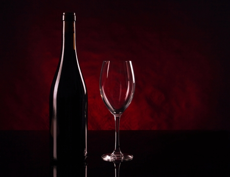 Bottle of red vine and empty vineglass Stock Photo