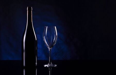 Bottle with vine and empty vineglass