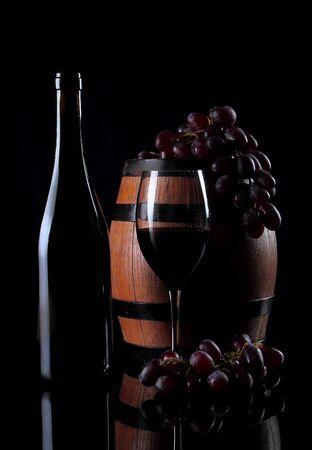 Bottle with vine on black background