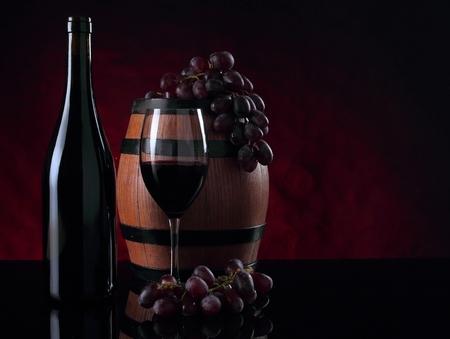 Bottle of vine, barrel, vineglass and grapes