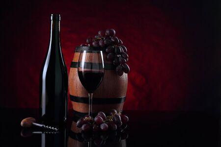 Red vine bottle, old wooden barrel and grapes