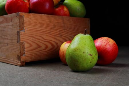 Juicy pears and apples. Autumn fruits in a wooden box. Stock Photo