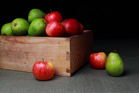 Red, green, sweet pear and an apple in an old wooden box on a dark background Stock Photo